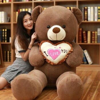 Woman sitting beside a 100 cm giant brown teddy bear holding an i love you pillow