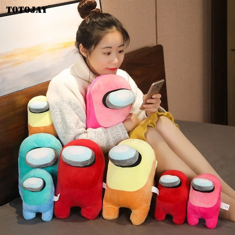 Woman playing with her mobile phone with multiple among us plushies