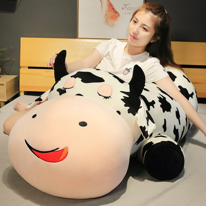 Woman sitting beside a giant cow stuffed animal