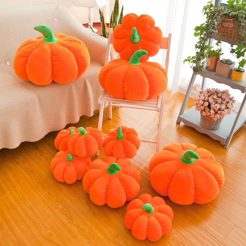 Multiple Plush Pumpkin in a bed room